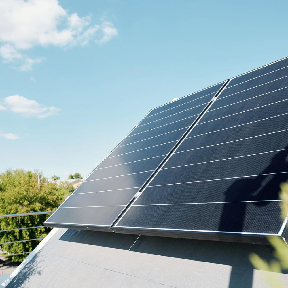 Large solar panels on rooftop of modern comfortable house or cottage in natural environment